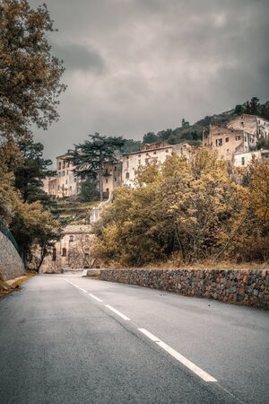 Road leading to the ancient mountain village of Ville di Paraso in the Balagne region of Corsica under dark storm clouds Stock Photo