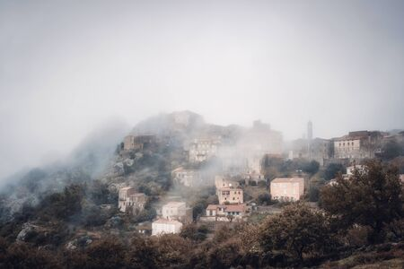 The ancient mountain village of Speloncato shrouded in mist in  in the Balagne region of Corsica Stock Photo