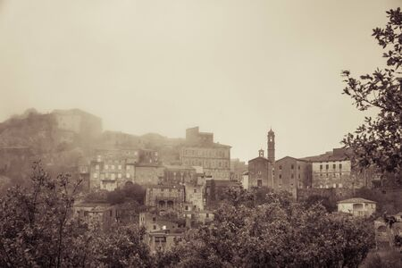 Sepia image of the ancient mountain village of Speloncato shrouded in mist in  in the Balagne region of Corsica