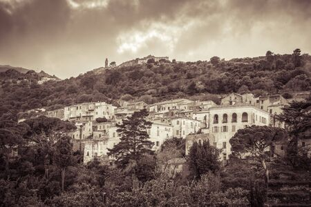 Sepia image of the ancient mountain villages of Ville di Paraso and Speloncato in the Balagne region of Corsica under dark storm clouds 版權商用圖片 - 134808223
