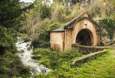 Ancient stone wash house standing by a fast flowing stream in the ancient mountain village of Ville di Paraso in the Balagne region of Corsica Stock Photo