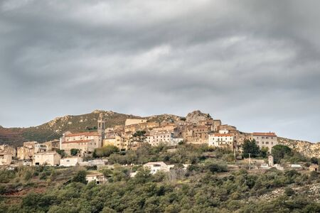 The ancient mountain village of of Speloncato in the Balagne region of Corsica under dark storm clouds Stock Photo