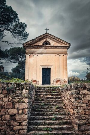 A stone mausoleum in the ancient mountain village of Ville di Paraso in the Balagne region of Corsica under dark storm clouds