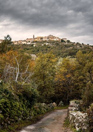Small track leading to the ancient mountain village of Speloncato in the Balagne region of Corsica under dark storm clouds 版權商用圖片 - 134808229