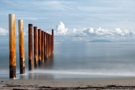 Long exposure image of rusty metal posts of breakwater on a sandy beach in Corsica lit up by the early morning sun against a calm Mediterranean sea with the island of Elba in the distance