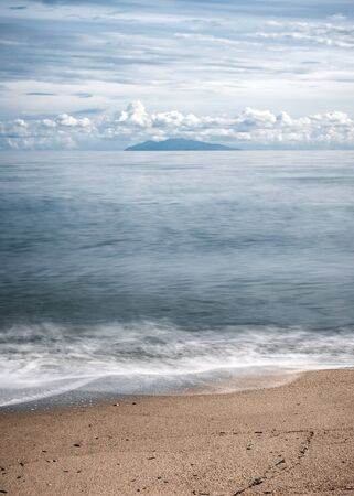 Long exposure image of waves washing onto a sandy beach in Corsica with the island of Elba silhouetted against the morning sky in the distance Stock Photo