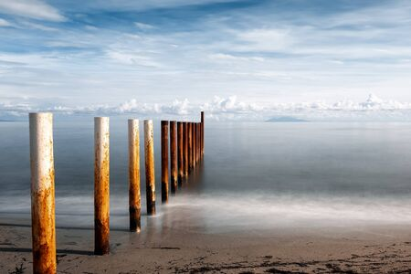 ong exposure image of rusty metal posts of breakwater on a sandy beach in Corsica lit up by the early morning sun against a calm Mediterranean sea with the island of Elba in the distance Stock Photo