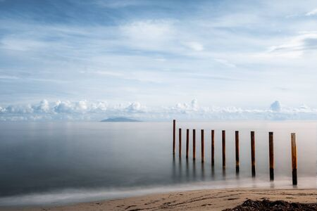 Long exposure image of breakwater on a beach in Corsica silhouetted by the early morning sun against a calm Mediterranean sea with the island of Elba in the distance Stock Photo