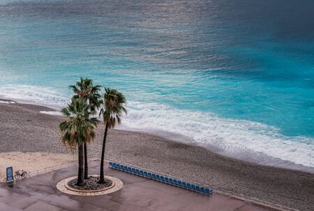 Three palm trees stand next to an empty row of chairs on the sea front on the Promenade des Anglais in Nice against the turquoise Mediterranean sea