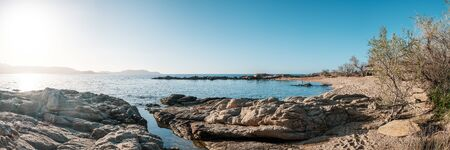 Panoramic view of turquoise mediterranean sea lapping gently onto the white sands and rocks at Arinella beach in the Balagne region of Corsica under a deep blue sky with Calvi citadel in the distance