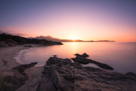 Long exposure image of sun setting over the golden sand of Plage de Sainte Restitude beach in the Balagne region of Corsica with the citadel of Calvi silhouetted in the distance