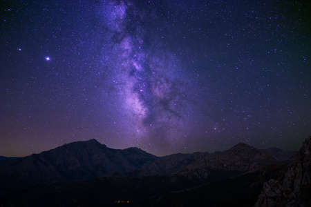 Milky Way passing over the church in the village of Pioggiola and the peaks of Monte Padru and Monte San Parteo in Corsica