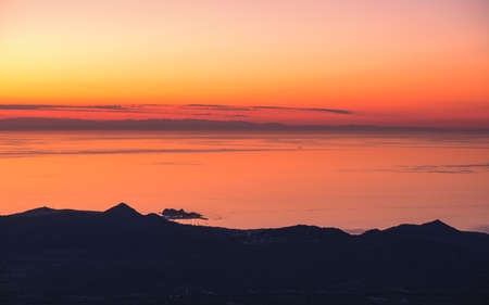 Sunset over Ile Rousse and the Mediterranean sea on the west coast of Corsica with the silhouetted coastline of mainland France in the distance