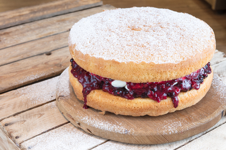 Victoria Sponge cake with fruit jam and vanilla cream on rustic wooden cake stand dusted with icing sugar.