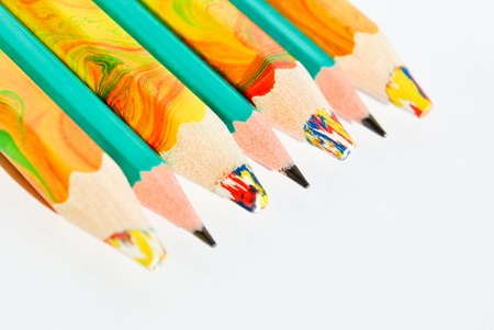 Different pencils placed diagonally isolated on white background photo