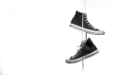 Black and white shot of pair of sneakers hanging in front of a white background Reklamní fotografie