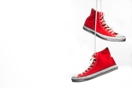 Red pair of canvas sneakers hanging in front of a white background Stock Photo