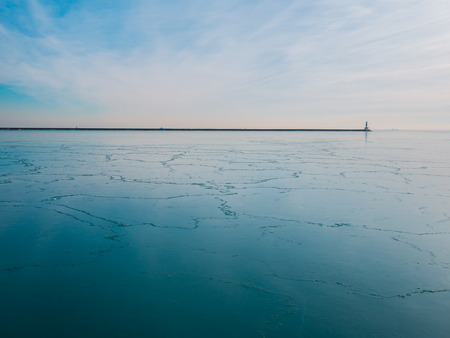 cracks in ice: A shot of a frozen lake with cracks in the ice leading up to the horizon Stock Photo