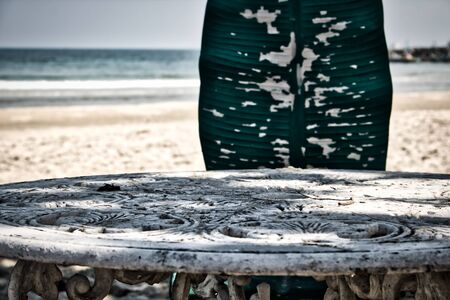 This unique photo shows an old metal table with beautiful ornaments and the broken chair and the sea in the background
