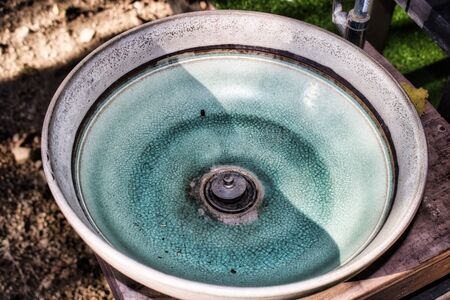 This unique photo shows an old green ceramic wash bowl that has been weathered by the sun and the paint has already cracked. The picture was taken in Hua Hin Thailand