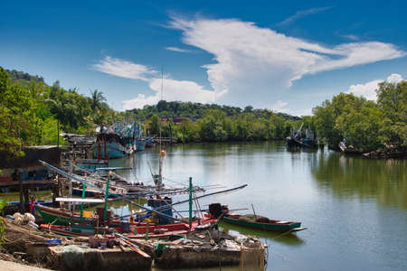 This unique photo shows the small old traditional fishing port with old wooden boats on a river in Pak Nam Pran in Thailand.