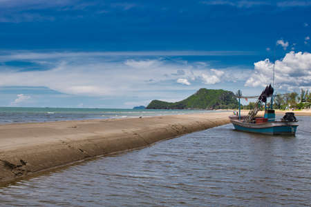 This unique photo shows a fishing boat running aground on the beach in Thailand and the Pak Nam Pran mountain range in the background