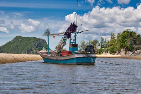 This unique photo shows a fishing boat running aground on the beach in Thailand and the Pak Nam Pran mountain range in the background Reklamní fotografie