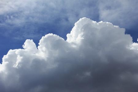 Billowing cumulus cloud against blue sky. Imagens