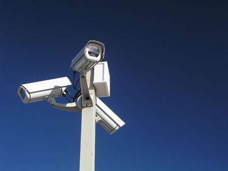 Three security cameras against blue sky Stock Photo