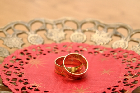 golden wedding rings on the red background photo
