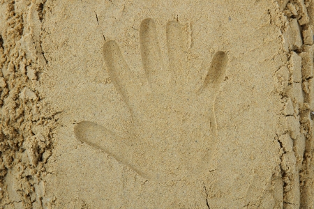 hand print in the sand as nice summer background photo
