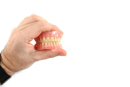 periodontics: teeth prosthesis in human hand isolated on the white background