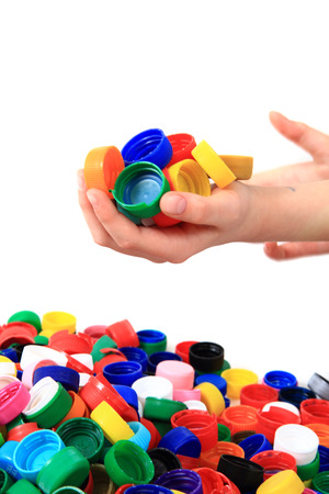 color plastic caps in human hands isolated on the white