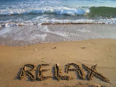relax - text in the sand  near the blue sea  photo