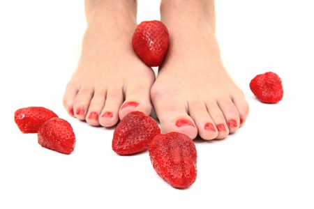 woman feet and strawberries isolated on the white background photo