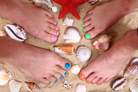 french pedicure: womens legs in the sand and shells as nice background Stock Photo