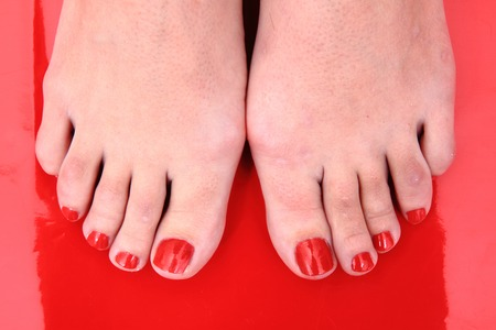 red nails on the feet on the red background photo