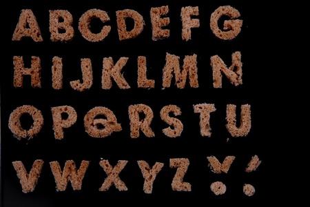 bread alphabet isolated on the black background photo