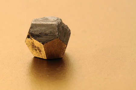 pyrite: pyrite gold crystal isolated on the golden background