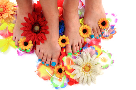 french pedicure: women feets and flowers as nice pedicure background