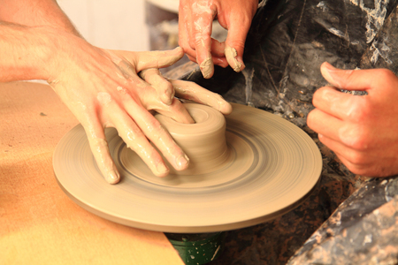 disciples: Artists hands shape clay into a fictility on a spinning wheel.