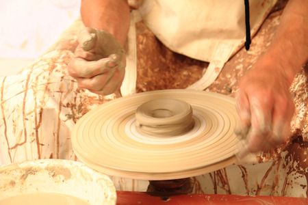 Artists hands shape clay into a fictility on a spinning wheel