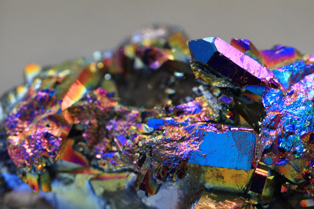 iron oxide: crystal with metal rainbow surface isolated on the grey background
