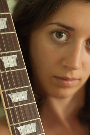 Guitar fretboard on the background of the girls face. Photo Stok Fotoğraf