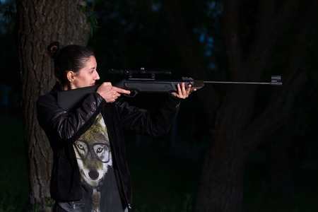 Girl with a gun in the woods. Photo. Stockfoto