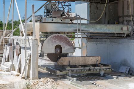 Machine cutting a granite block. Photo