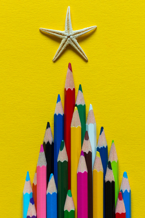 Colored pencils laid out in a pyramid. On top of the pencil starfish. On a yellow paper background. Photo.