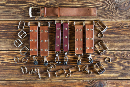On brown wooden table leather belts and accessories. Photo.