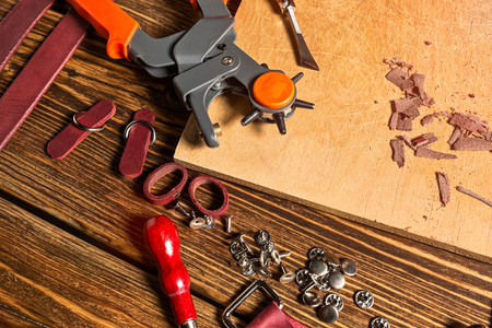 On brown wooden table scattered with tools and accessories for working with leather. Photo.