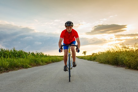 The cyclist in red blue form rides along fields of sunflowers. In the background sunset sky. Goes to camera. Horizontally framed shot.